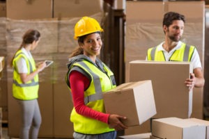 Smiling female warehouse worker holding a box.